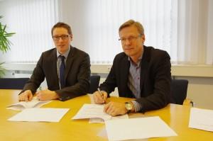 Komnexx-Geschäftsführer Silas Bittmann und GWW Geschäftsführer Otto Steinkamp (von links) unterzeichnen den Pachtvertrag für das Glasfasernetz der Gemeindewerke Wallenhorst.
